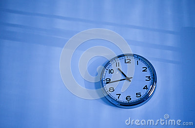 Blue clock on a blue wall