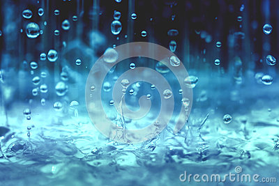 Blue color tone of close up rain water drop falling to the floor in rainy season Stock Photo