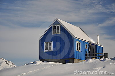 Blue cottage covered by snow, Greenland