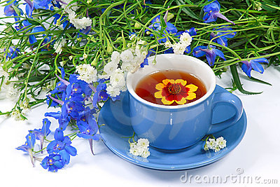 The blue cup of tea with flowers
