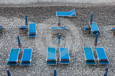 Blue deckchairs on stony beach