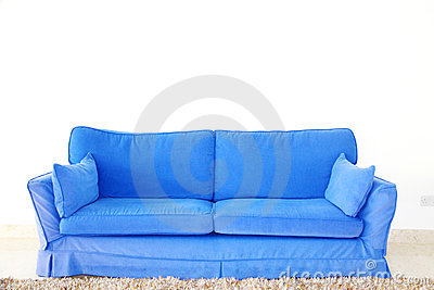 Blue double sofa on a blank wall