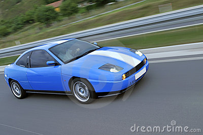Blue fast racing car on the highway