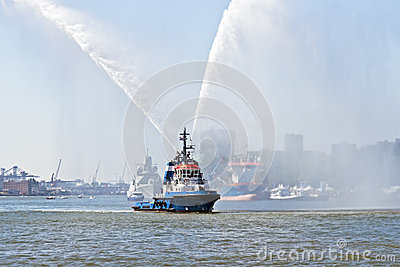 Blue fire boat spraying water in Rotterdam harbor Netherlands