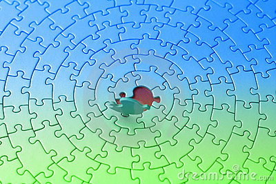 Blue-green jigsaw with the last piece upstanding
