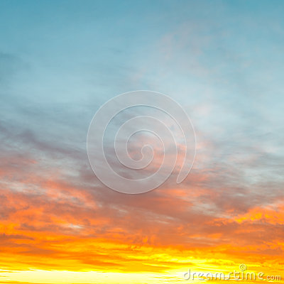 Blue morning sky over yellow sunrise clouds