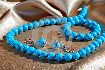Blue necklace and earrings on a brown