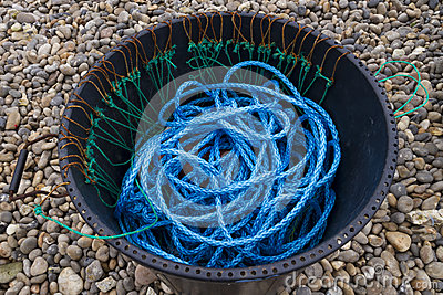 Blue Nylon Rope, black bin, pebbled beach