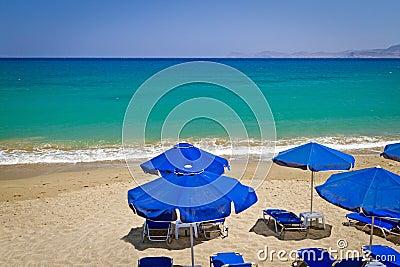 Blue parasols at Aegean Sea