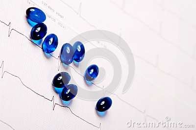 Blue pills on ECG chart (electrocardiogram)