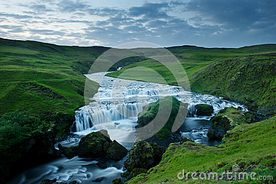 Blue river among green hills at the sunset South Iceland