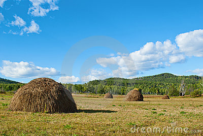 Blue sky and clouds over green hills with haystack