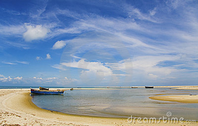 Blue sky, white clouds, boat on a sandbank, sea