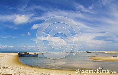 Blue sky, white clouds, boat on a sandbank, sea