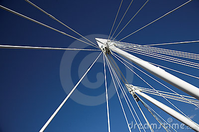 Blue sky and white strings of a bridge
