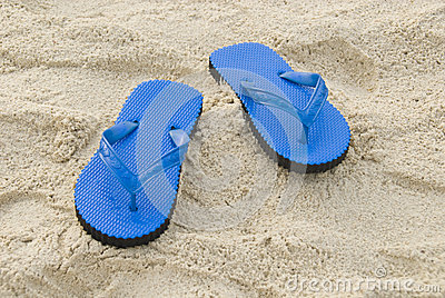 Blue slipper on a sandy beach