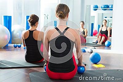 Blue toning ball in women pilates class rear view