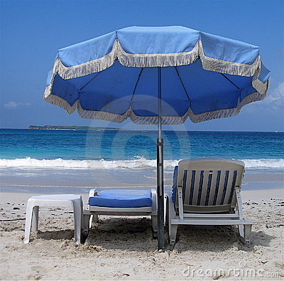 Blue umbrella and deckchairs