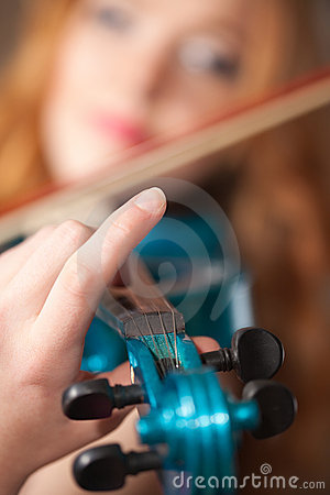 Blue violin in focus at artist s hand