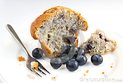 Blueberry muffin with fresh fruit on white plate