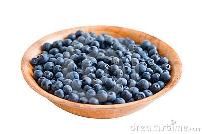 Blueberry in round wooden plate. Isolated on white