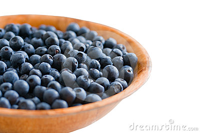 Blueberry in wooden plate. Isolated on white.