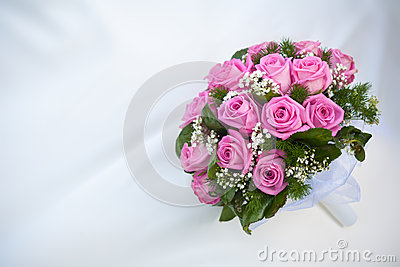 Blumenstrauß der rosafarbenen Rosen auf dem weißen Hochzeitskleid