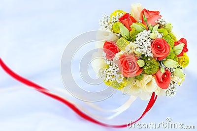 Blumenstrauß von Rad-Rosen auf dem weißen Hochzeitskleid