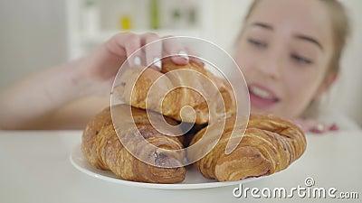 Bluriges kaukasisches Mädchen, das sich umherschaut und frisch köstliche, krustende Croissants beißt Junge Frau bricht Diät Selbs stock video footage