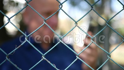 Blurred Image with a Happy Man Texting Using Cellphone from a Protection Area.  stock footage