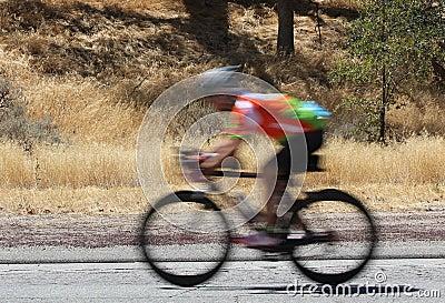 A blurred image of a speeding bike rider.