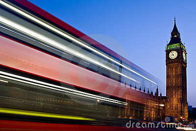Blurred London double-decker bus passes Big Ben