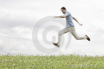 Blurred motion of young man jumping in park against sky