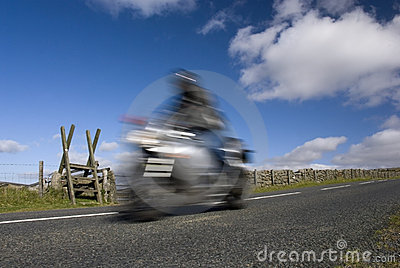 Blurred speeding motorbike on mountain road
