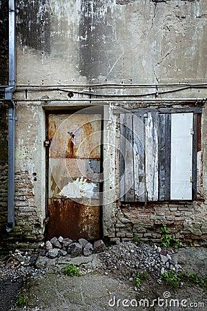 Boarded up window and rusty door