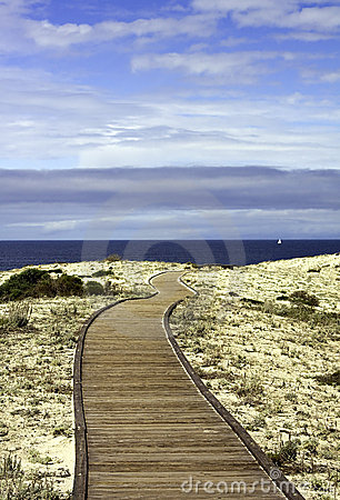 Boardwalk over sand dunes with blue sky and clouds