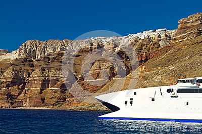 Boat at high volcanic cliff of Santorini island