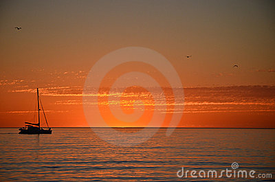 A boat on the horizon at sunset