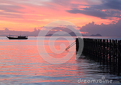 Boat and jetty on sunset sea