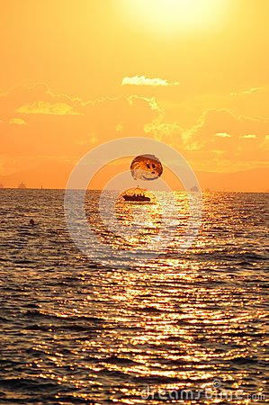 Boat with a parachute at sunset