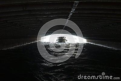 Boat sailing under bridge