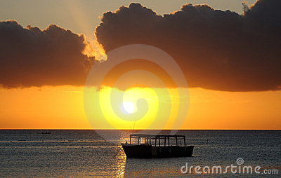 Boat silhouetted at sunset