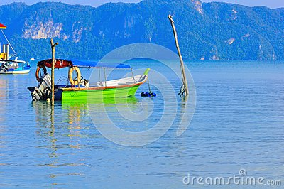 Boat tied to two wooden poles in Langkawi Island Editorial Stock Image