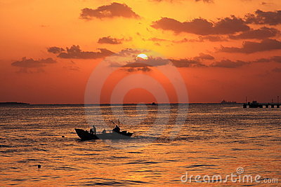 Boat on water at sunset