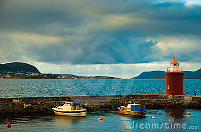 Boats and beacon in harbor. Alesund, Norway