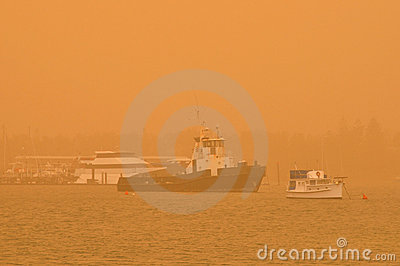 Boats lie at anchor in a dust storm over the ocean