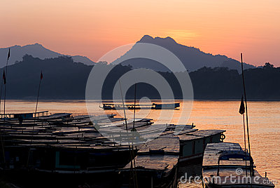 Boats on the mekong river by sunset