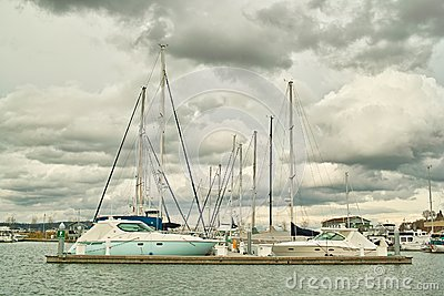 Boats in moorage against clouds