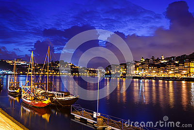Boats moored along the riverfront with lights reflecting in the Douro River in Porto, Portugal Editorial Photography