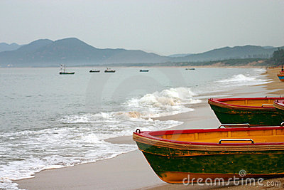 Boats moored on beach by sea